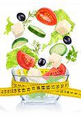 Falling Greek Salad In A Glass Salad Bowl. Concept Slim Figure