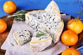 Blue cheese with sprigs of rosemary and oranges on metal tray with sheet of paper and color wooden table background