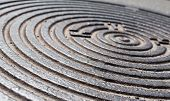 picture of manhole  - Metal manhole cover with circular relief surface. Close up. ** Note: Shallow depth of field - JPG