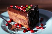Delicious chocolate cake decorated with pomegranate seeds on plate on table
