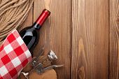 Red wine bottle and corkscrew over rustic wooden table background with copy space