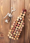 Wine bottle shaped corks and corkscrew over rustic wooden table background. View from above