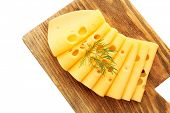 Sliced cheese with dill on wooden cutting board isolated on white background