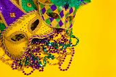 A group venetian, mardi gras mask or disguise on a yellow background with strings of beads