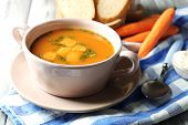 Carrot soup, cream and spoon, on  color wooden background