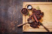 Sliced Medium Rare Grilled Beef Steak Ribeye With Salt And Pepper On Meat Cutting Board On Dark Wood