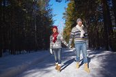 Amorous and ecstatic couple taking walk in winter forest