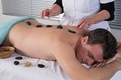 Man Getting Stone Therapy Massage In  Spa