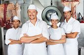 Portrait of mature male butcher with confident team in butchery