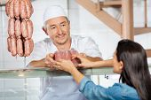 Mature male butcher giving pack of sausages to female customer in butchery