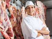 image of slaughterhouse  - Portrait of happy mid adult female butcher standing arms crossed in slaughterhouse - JPG