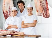 Portrait of confident male and female butchers standing together at counter in shop