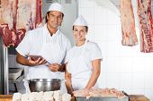 Portrait of confident male and female butchers with digital tablet at counter in shop