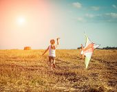foto of kites  - happy little girl with a kite in a field - JPG
