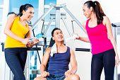 Women teasing man at gym