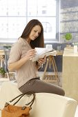 Young woman sitting on backrest of sofa, checking mail as arriving at home.