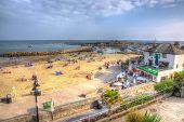 Sunny warm weather brought visitors and tourists to Lyme Regis Dorset in HDR like painting