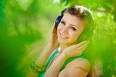 Smiling woman with headphones in the Park.