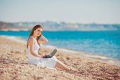 Young woman with laptop on the beach near the sea.