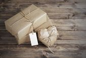 Heart And Box Wrapped In Brown Kraft Paper With A Price Tag,  On Wooden Table Closeup