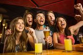stock photo of cheer  - Happy friends drinking beer and cheering together in a bar - JPG