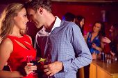 stock photo of half-dressed  - Cute couple drinking cocktails together at the nightclub - JPG
