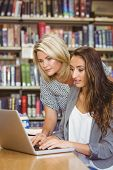 Blond mature student helping her classmate in library