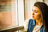 Pretty brunette sitting alone unsmiling against a window