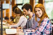 image of classmates  - Student looking at camera while studying with classmates in library - JPG