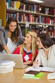 Pretty student showing her classmates something on laptop in library