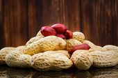 stock photo of groundnut  - Peeled peanut on well peanuts on wooden background - JPG