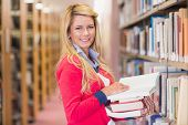 Mature student picking out book in library at the university