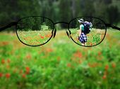 Woman young backpacking in wildflowers taking photograph blurred with glasses