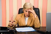 Worried Elderly Woman Working In Office