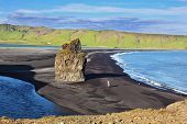The cape Dirkholaey in the south of Iceland. On beach with black volcanic sand there is  huge rock in the form of palm
