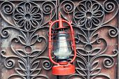 Kerosene lamp on wrought iron gates background