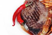 entree : grill beef meat steak on white round plate with dry hot chili pepper and potato chips isolated on white background