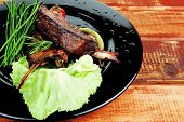 served meat: spiced barbecued ribs on black plate with vegetables