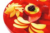 image of cold red jelly cake with nectarine and peach