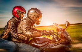 image of biker  - Couple Bikers in a leather jacket riding a motorcycle on the road - JPG