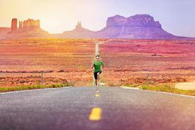 stock photo of sprinters  - Runner man athlete running sprinting on road by Monument Valley - JPG