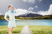 pic of air hostess  - Pretty air hostess with hand on hip against scenic backdrop - JPG