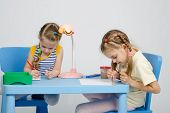picture of 6 year old  - Two girls of four and six years of sitting at the table and draws and paints and pencils - JPG