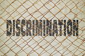picture of racial discrimination  - Conceptual image with the word Discrimination under a wire netting - JPG