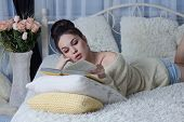stock photo of short-story  - Attractive girl reading a book lazily at home - JPG