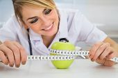 foto of measurements  - Happy Female Dietician Measuring Green Apple With Measuring Tape  - JPG
