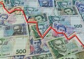 picture of descending  - Ukrainian banknotes background and descending graph - JPG