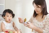 foto of child feeding  - Asian mother feeding her child at home - JPG