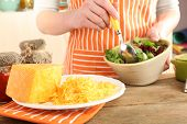 stock photo of grating  - Woman cooking salad with grating cheese - JPG