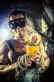stock photo of greenpeace  - Strong muscular man coal miner holding a flower in a pot over dark grunge background - JPG